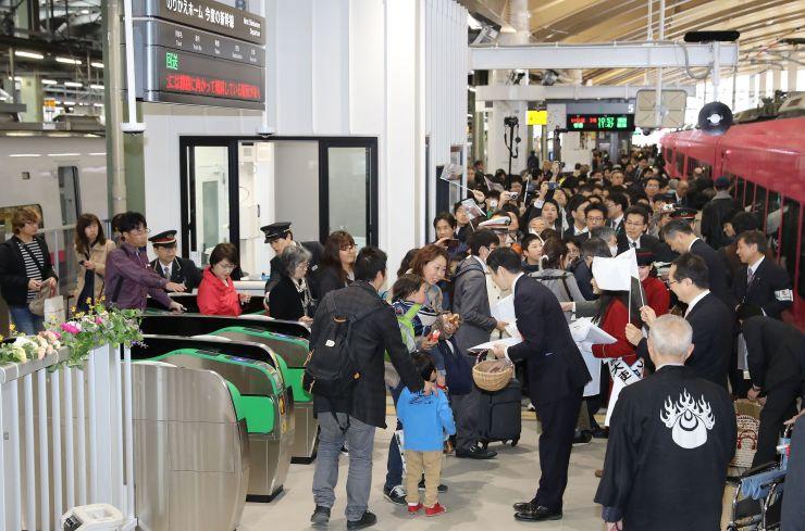 上越新幹線から特急「いなほ」への乗り換え客を関係者が歓迎し、にぎわう同一ホーム=15日、JR新潟駅