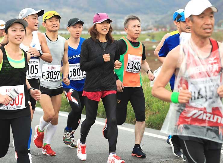 ゴールまで残り10キロ付近、ランナーと一緒に走る高橋尚子さん=15日、長野市松代町岩野