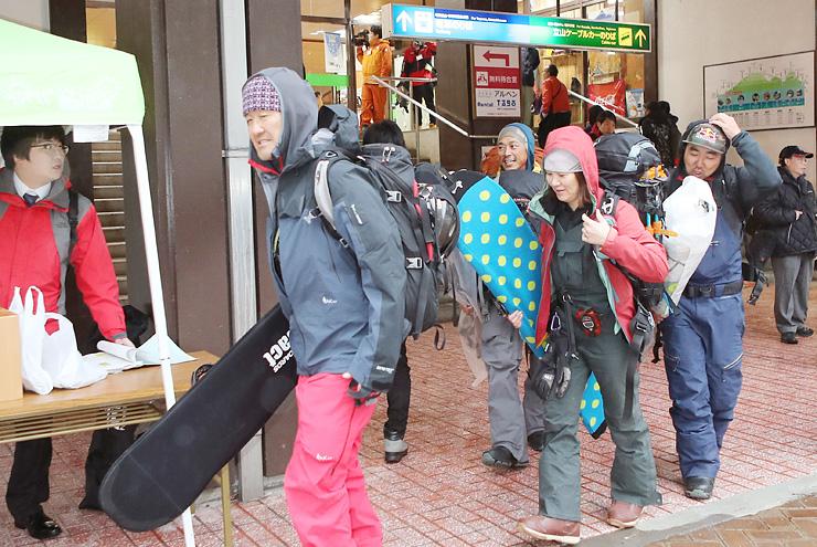 高原バスの終日運休が決まり、がっかりした様子で立山駅を後にするスノーボーダーら