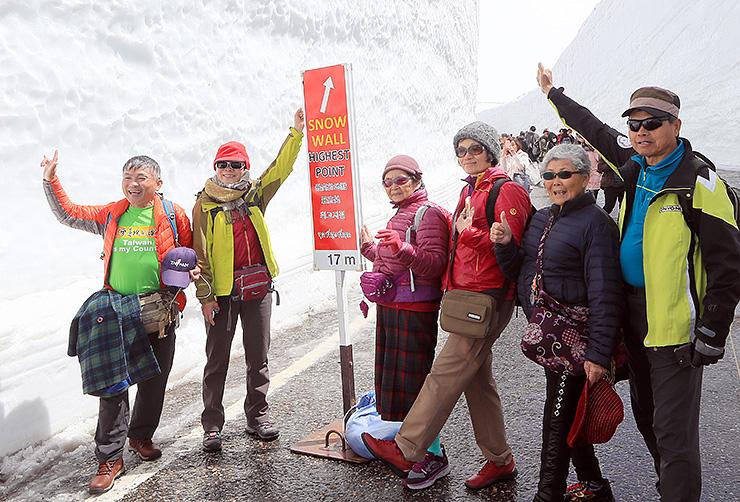 雪の壁をバックに記念撮影する観光客=立山・雪の大谷
