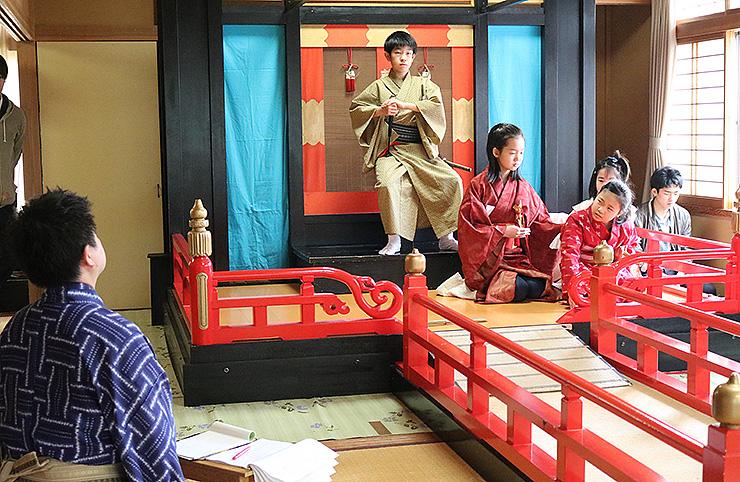 堀内さん(左)の指導を受けながら、せりふや動きのタイミングを確認する児童