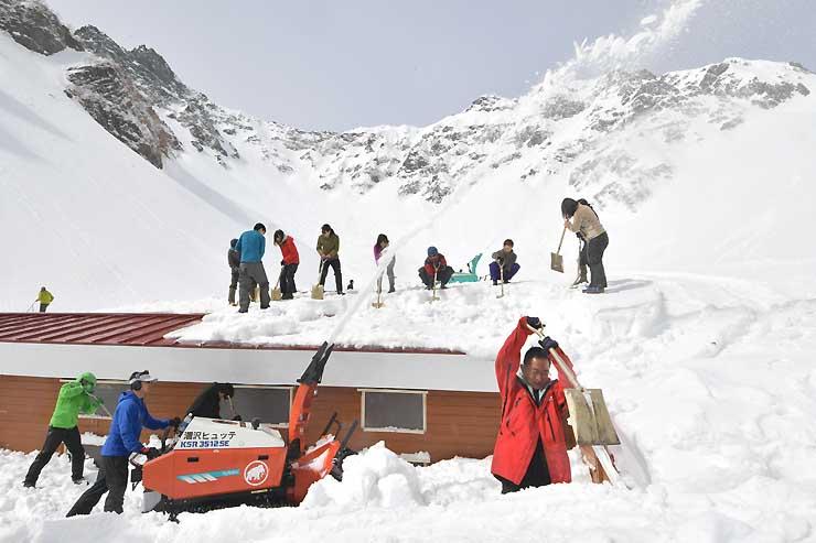 雪をまとったカールを背景に小屋の除雪作業が進む涸沢ヒュッテ=17日午前9時6分、松本市安曇