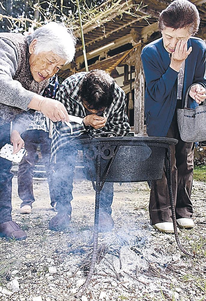 湯に浸した紙を目に当て、願い事をする住民=七尾市中島町小牧の小牧白山社