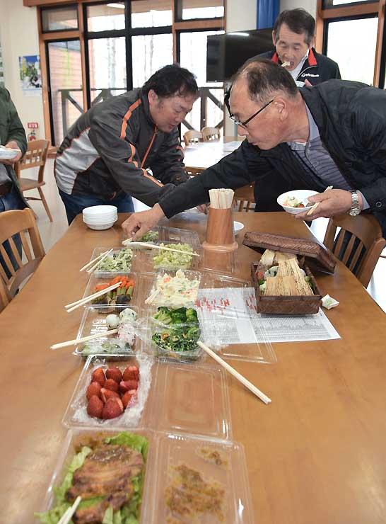 弁当に詰めるメニューを試食する参加者たち