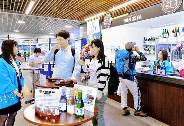 オープンした立ち飲みバーで早速地酒を味わう旅行客ら=4月23日、福井県福井市のJR福井駅コンコース