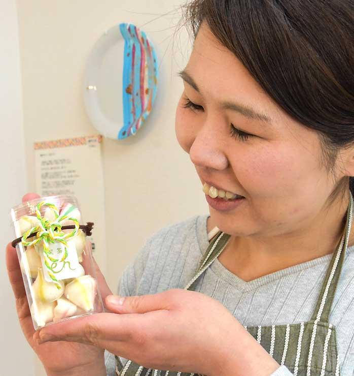 「水引メレンゲ」を手にする黒田さん。「幸せのお裾分けとして贈り物にもぴったり」