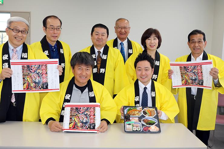 休憩コーナーで提供する弁当や包み紙を手にする着地型観光検討委メンバー