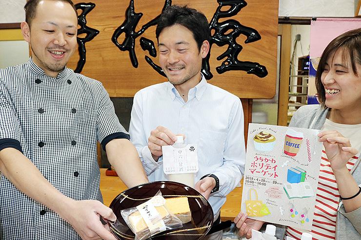 完成したカステラを前に笑顔の(左から)野村さん、板林専務、沼尻代表