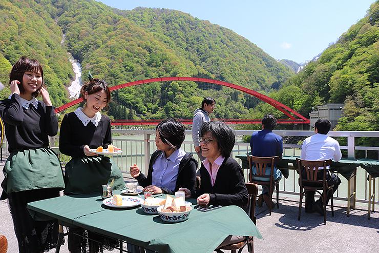 新緑に包まれたカフェで、津田さん(左から2人目)らと食事を楽しむ関係者=宇奈月ダム