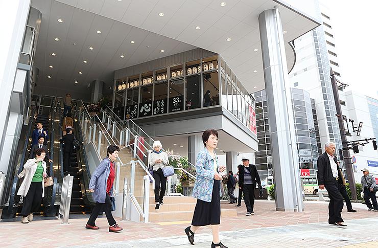飲食店などが開業した再開発ビル「パティオさくら」の入り口を行き交う人々=富山市桜町1丁目