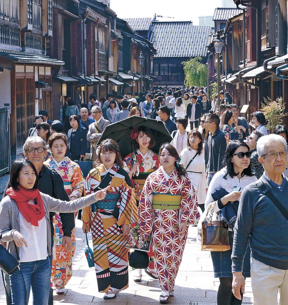 街並みの風情を感じながら散策を楽しむ観光客=金沢市のひがし茶屋街