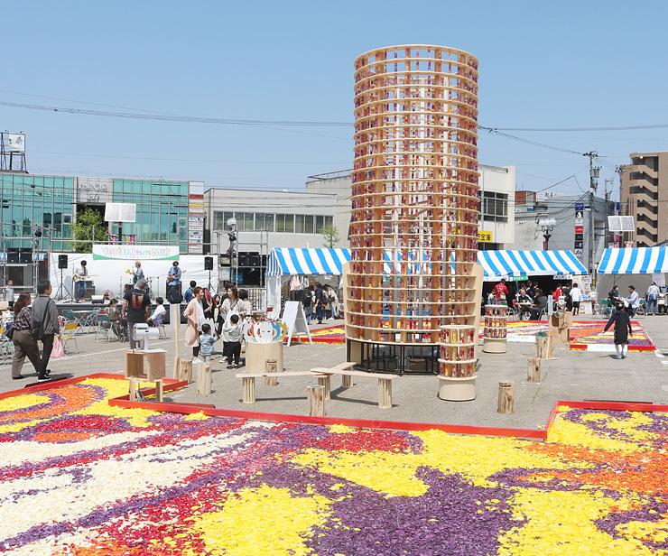 チューリップのハーバリウムを積み上げたタワーや花びらのじゅうたんを楽しむ来場者=JR砺波駅前広場