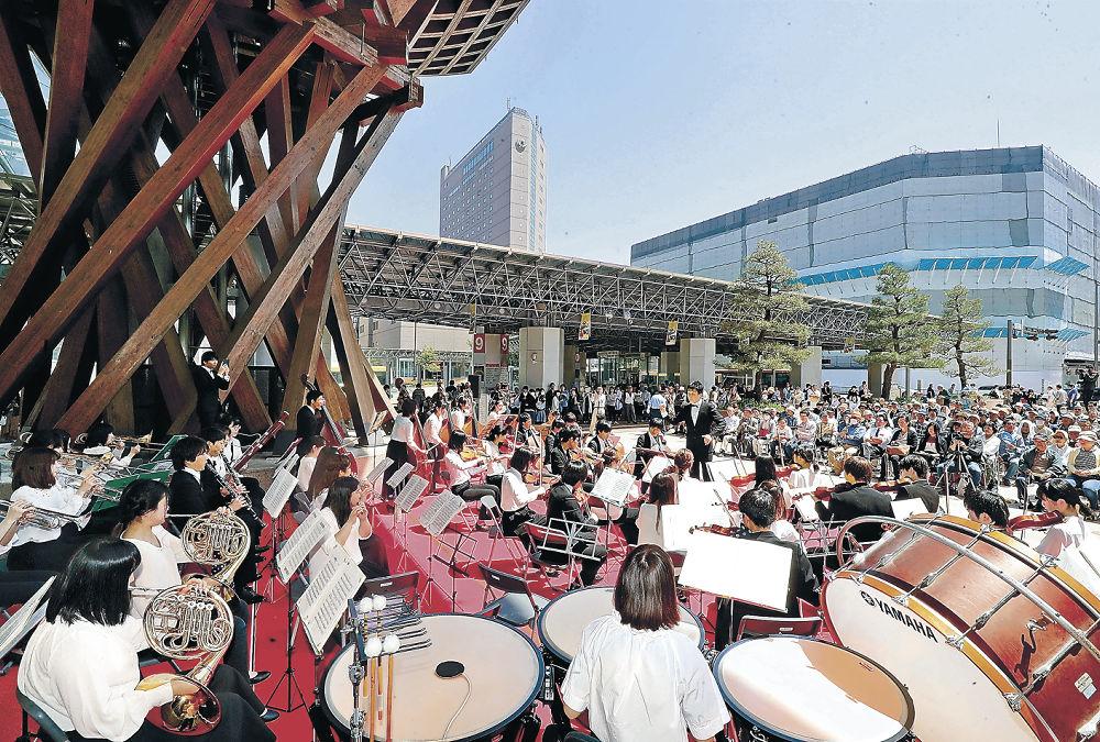 華やかな音色を広げた金大フィルハーモニー管弦楽団=金沢駅の鼓門