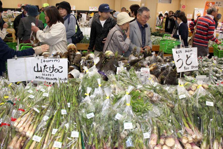 広々した売り場で地場産野菜などを買い求める客でにぎわった直売所=27日、上越市大道福田