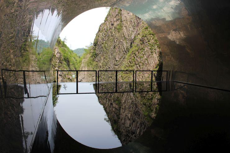 改修された清津峡渓谷トンネルのパノラマステーション。床の水と、壁のステンレス板に外の景色が映る=27日、十日町市小出