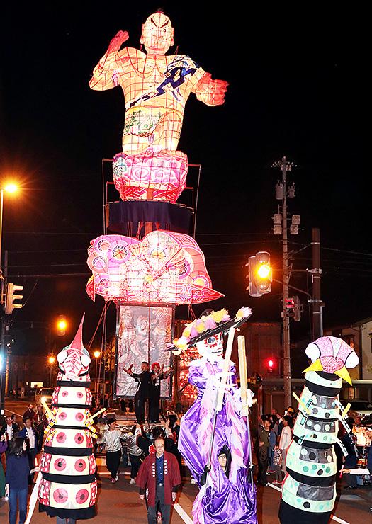 巨大人形(手前)に先導され、引き回される文久の大行燈=JR福野駅前
