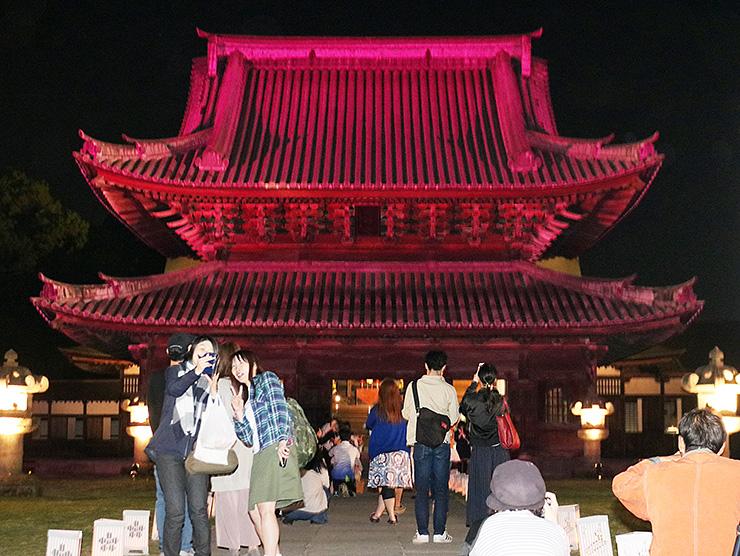 ライトアップされた仏殿前で記念撮影を楽しむ来場者=瑞龍寺