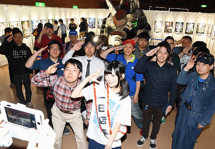 空野さん(手前右)と記念写真に納まる来場者たち。奥は被弾したガンダムの頭部=高岡テクノドーム