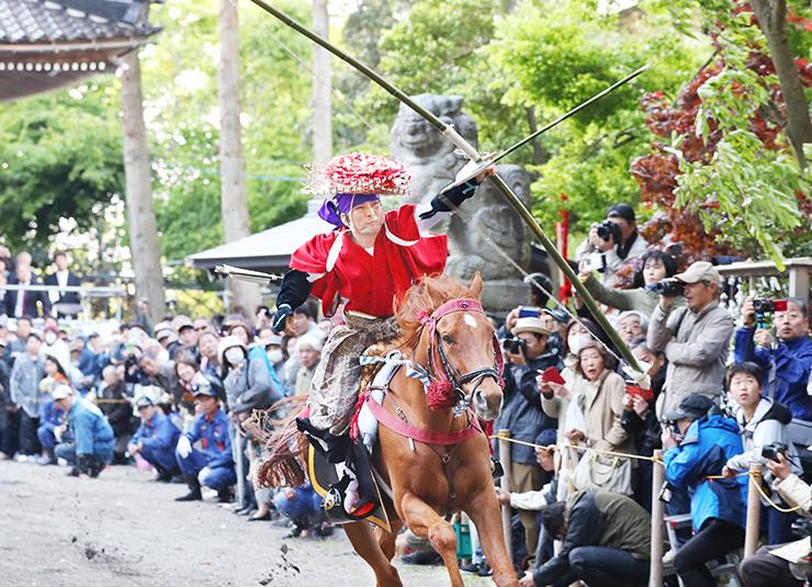 疾走する馬から矢を放つ武者姿の男性=下村加茂神社