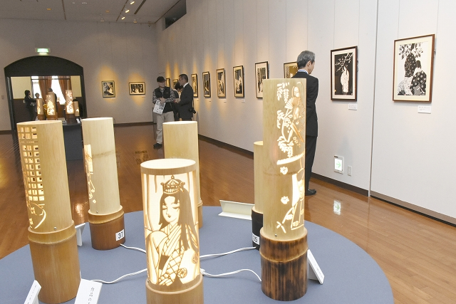 源氏物語を題材にした切り絵と竹灯籠が並ぶ企画展=福井県の越前市武生公会堂記念館