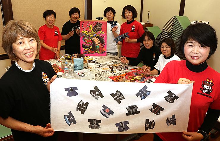 法被がデザインされた手ぬぐいを手にする筱岡支部長(右)と小松さん=津沢商工会館