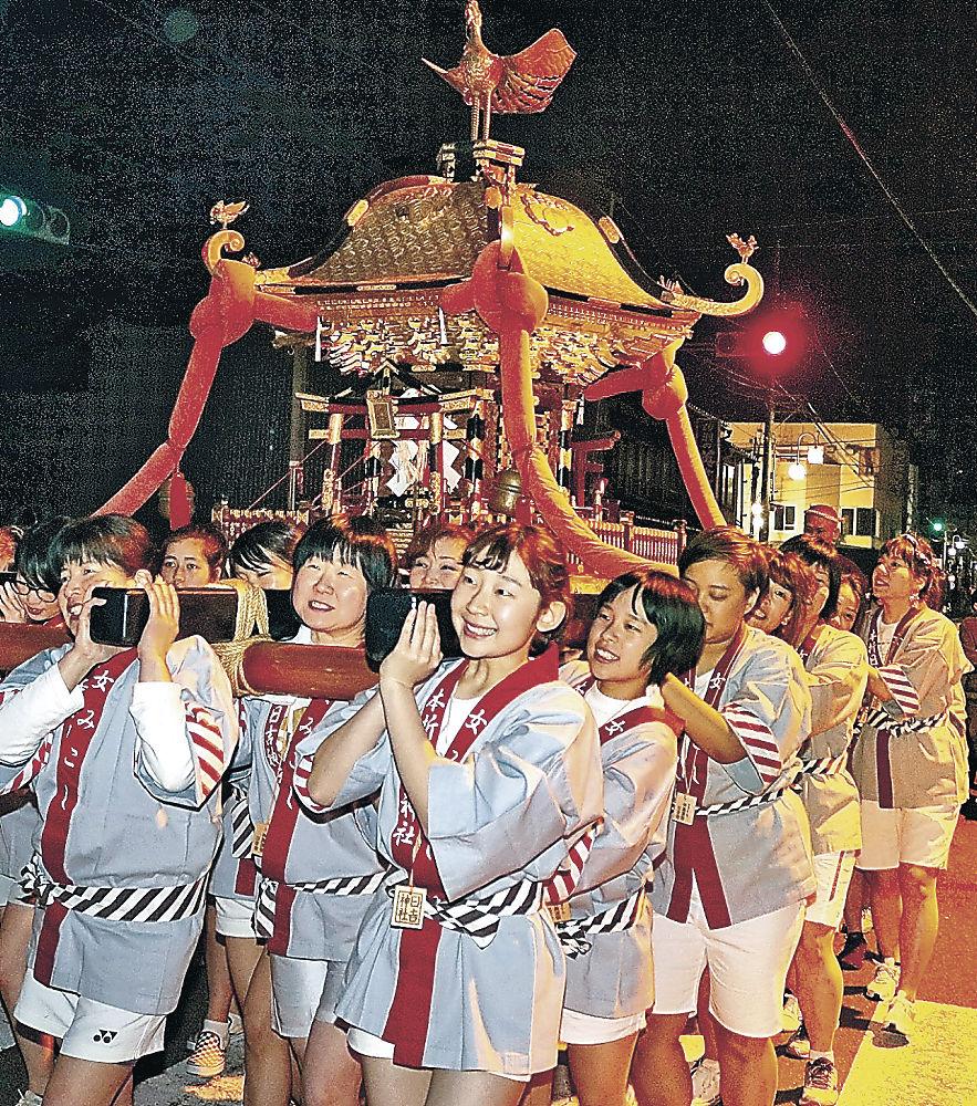 担ぎ手に加わった横井さん(中央)と、その後ろで担ぐ長尾さん=小松市本折町