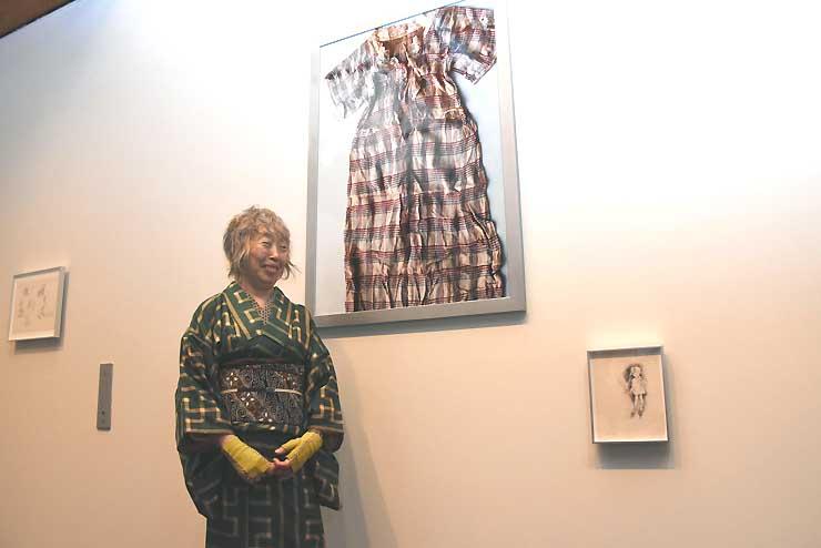 原爆犠牲者のワンピースを撮った写真(中央)の前に立つ石内さん