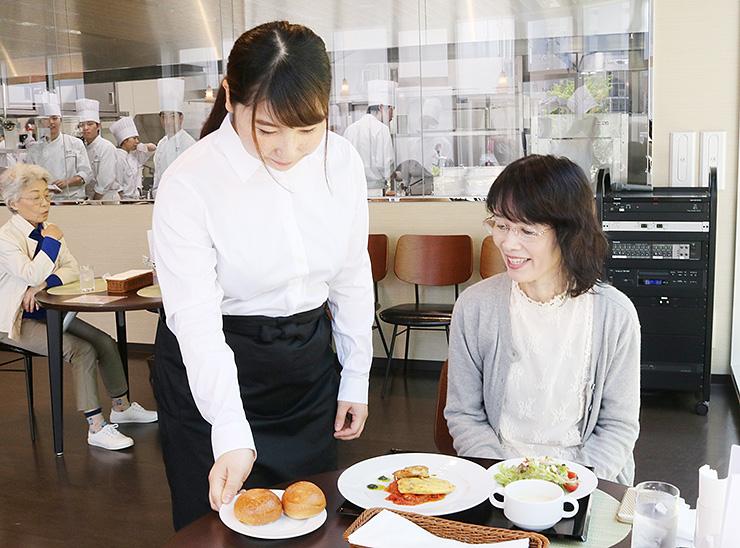 客にパンを運ぶ女子生徒。キッチンにいる生徒も様子を見守っている