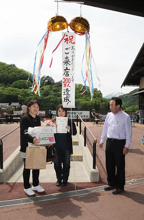 大橋社長(右)から記念品を贈られた西山さん(左)ら