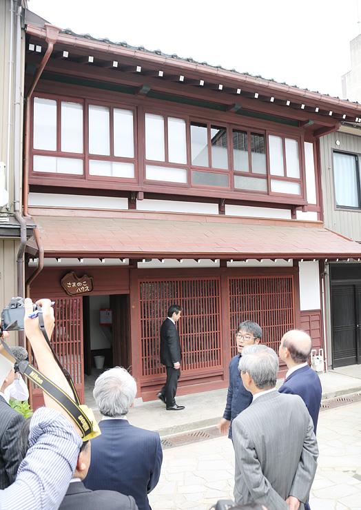 オープンした「さまのこハウス」の説明を受ける式典出席者=高岡市金屋町