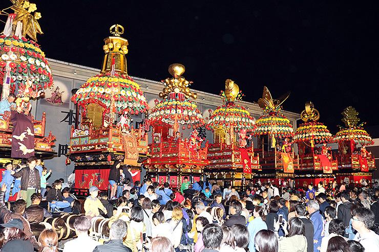 伏木曳山祭の本番を前にライトアップされる7本の花山車=高岡市伏木本町の山倉前