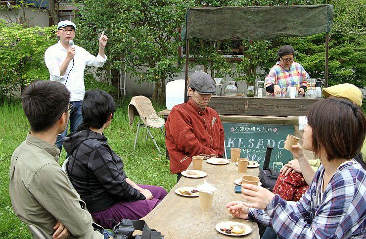 焙煎したコーヒーを振る舞うイベントで、コーヒーの魅力を語る沢村明亨さん(左奥)=佐渡市羽茂大崎