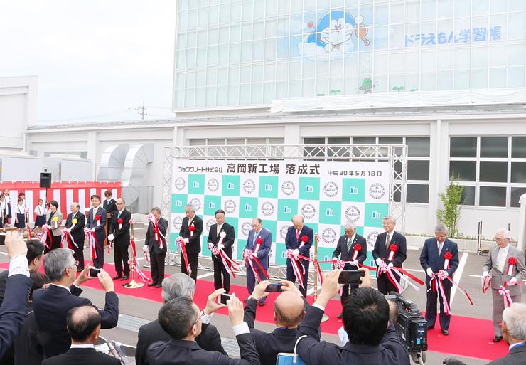 テープカットで新工場の完成を祝う出席者。後ろはドラえもんの壁画=ショウワノート