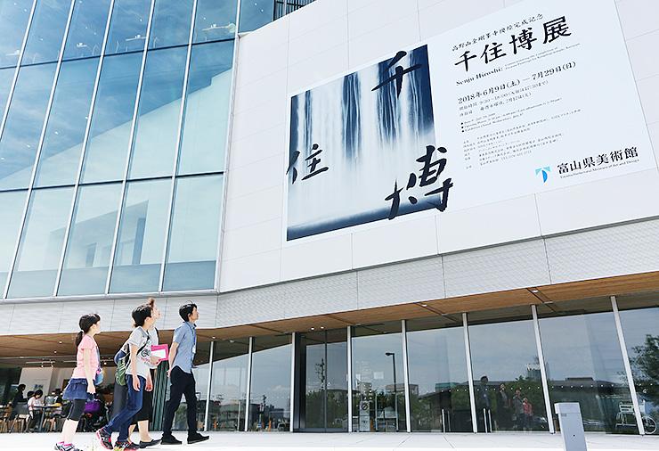 富山県美術館の外壁に掲げられた「千住博展」の巨大ポスター=富山市木場町