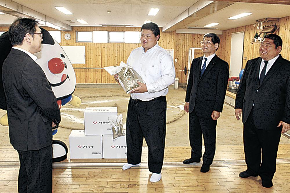川本次長(左)から石川県産コシヒカリを受け取る前田主将=金沢学院高