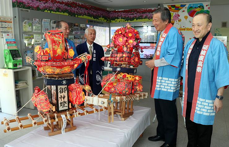 ミニ行燈を横に笑顔を見せる山田さん(右)と渡辺さん(右から3人目)。手前が山田さんの作品で、奥が渡辺さんの作品