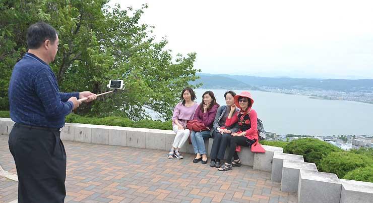 諏訪市の立石公園で諏訪湖を背に記念撮影する台湾からの観光客