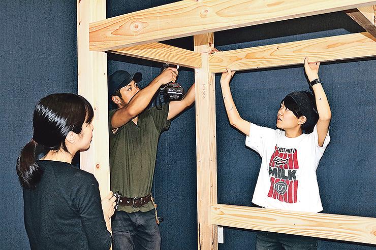 木製の2段ベッドを組み立てる荒木さん(右)ら=富山市奥田新町
