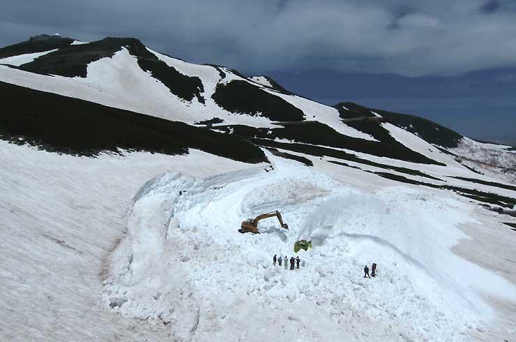 開通に向けて重機で除雪作業が進む県道乗鞍岳線=25日午前11時2分、松本市安曇(小型無人機で撮影)