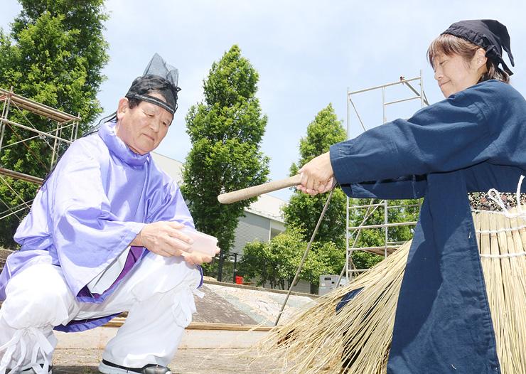 衣装を着て採火の流れを確認する野村さん(左)=富山市婦中町島本郷