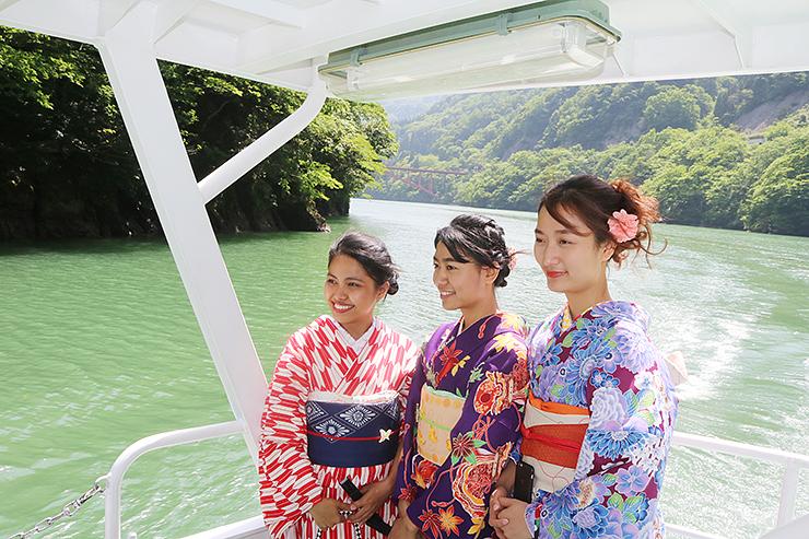 遊覧船で写真撮影する留学生