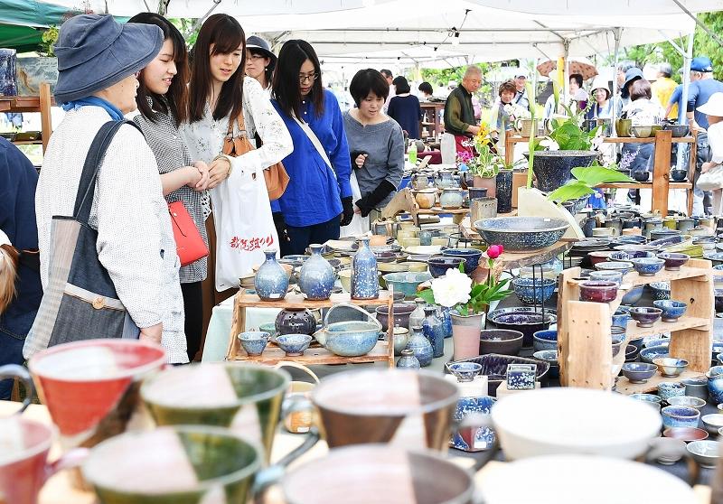 多彩な器類が並び、来場者でにぎわう陶器市=5月26日、福井県越前町小曽原の越前陶芸村