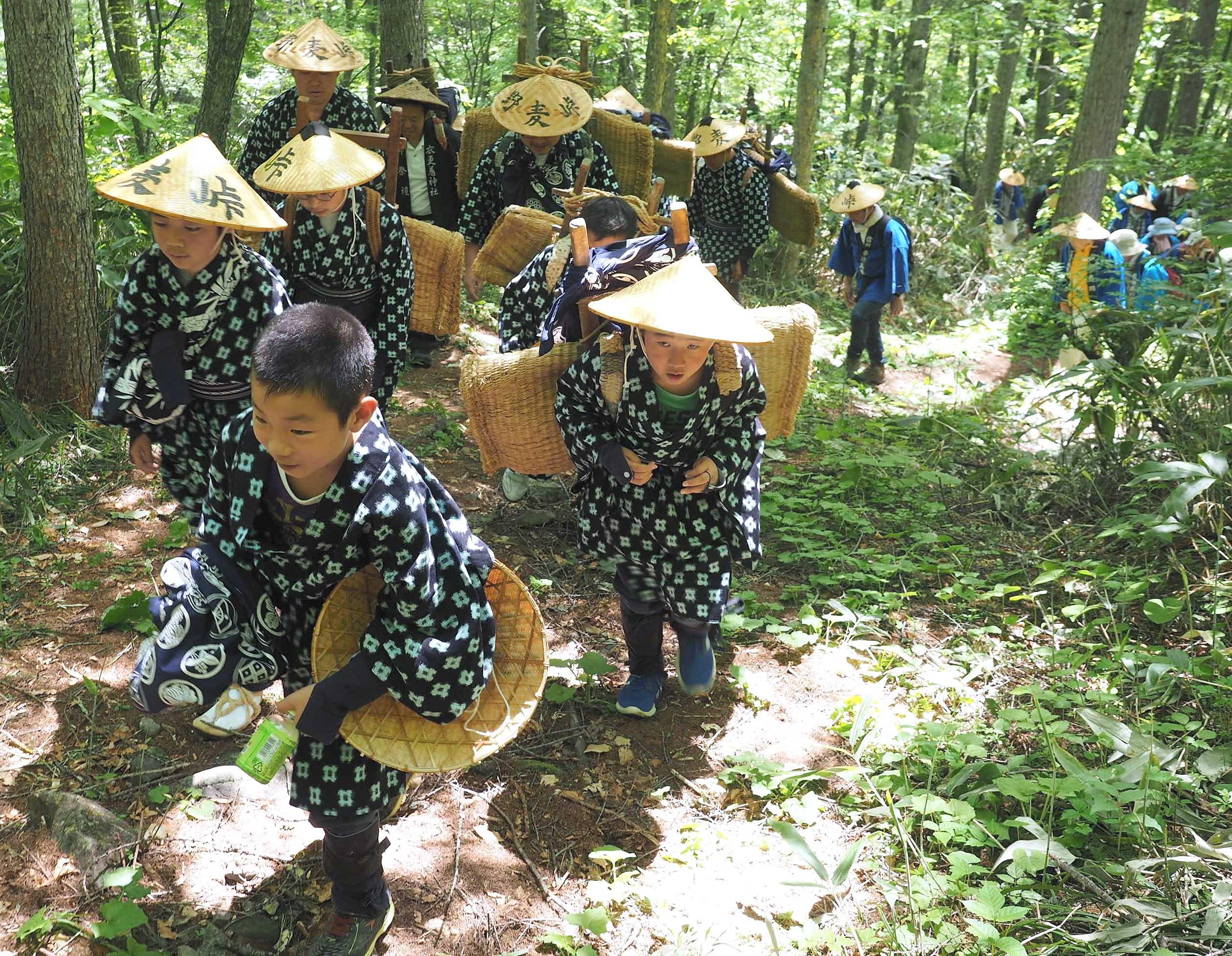 着物姿に、編みがさをかぶって峠の山道を歩く小学生たち