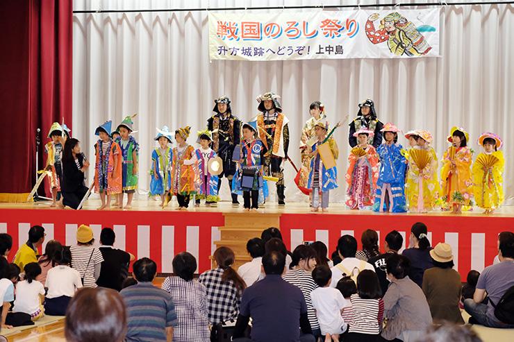 魚津もくもくホールのステージに上がり、手作りのよろいや着物を披露する上中島小の児童