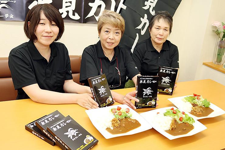 内容とパッケージを一新した「氷見カレー」を紹介する堀江会長(中央)と学会メンバー
