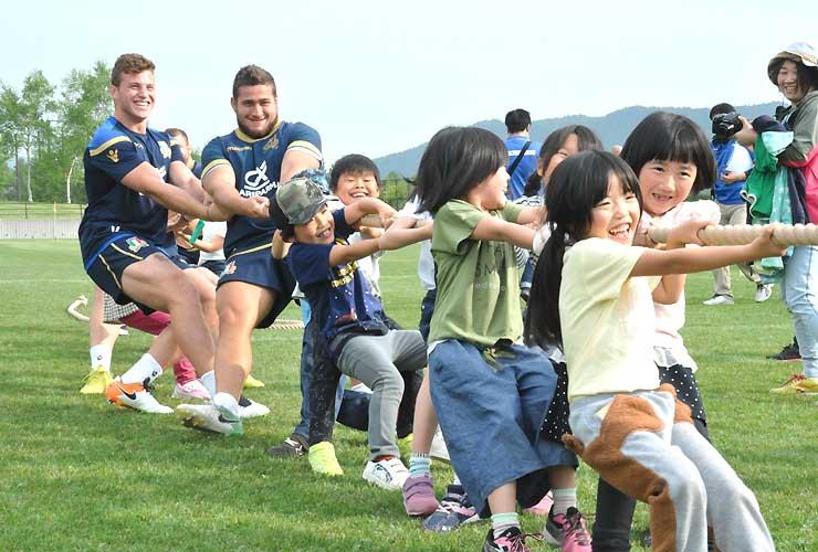 菅平小学校の児童らと綱引きを楽しむラグビー・イタリア代表の選手ら(奥)=上田市のサニアパーク菅平