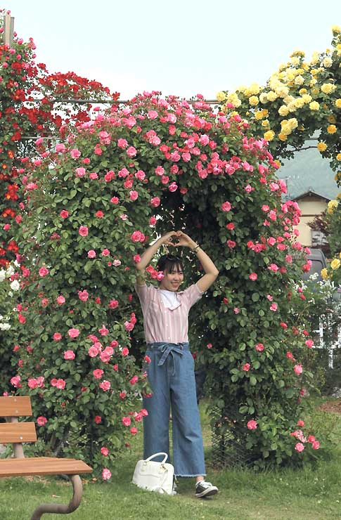 バラを背景にポーズを取って記念写真に納まる女性=27日、中野市の一本木公園