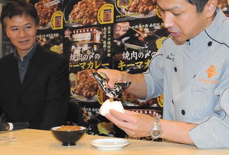 キーマカレーをおにぎりに付ける食べ方を実演する中田さん(右)
