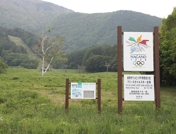 長野冬季五輪会場だったことを示す案内板が立つ飯綱高原スキー場。左奥の急斜面が里谷多英コース