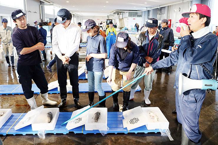 競り人(右)の掛け声に合わせ「いみずサクラマス」を競り落とす大勢の仲買人ら=新湊漁港